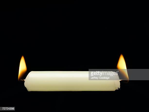 Horizontal candle with flame burning at each end, close-up