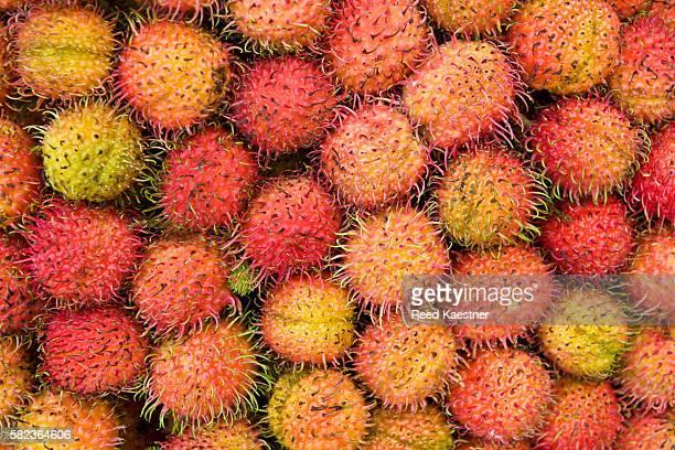 A horizontal close up photograph of Rambutan fruit in a stack