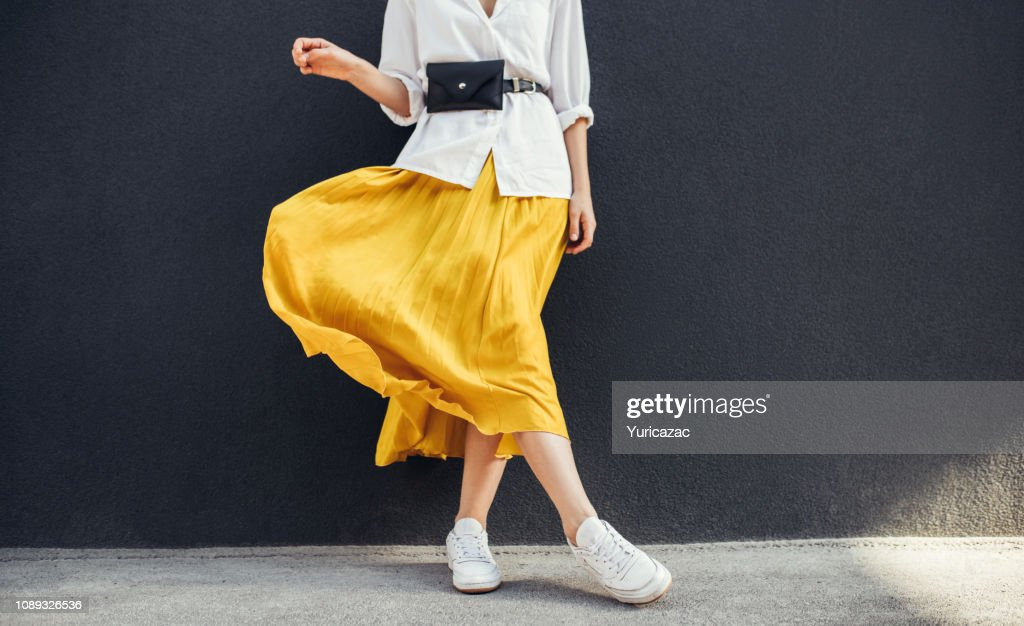Horizontal cropped image of stylish slim woman in beautiful yellow skirt. Caucasian female fashion model standing over gray wall background outdoor with copy space. : Stock Photo