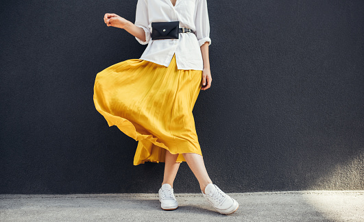Horizontal cropped image of stylish slim woman in beautiful yellow skirt. Caucasian female fashion model standing over gray wall background outdoor with copy space. 1089326536