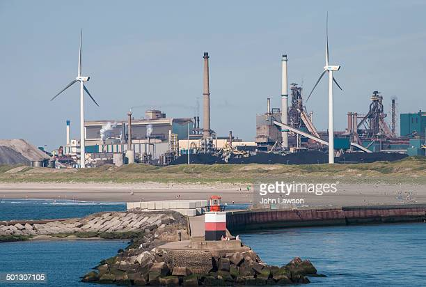CONTENT] A horizontal image of electricity generating windmills and a steel works IJmuiden and Velsen Noord North Holland Netherlands
