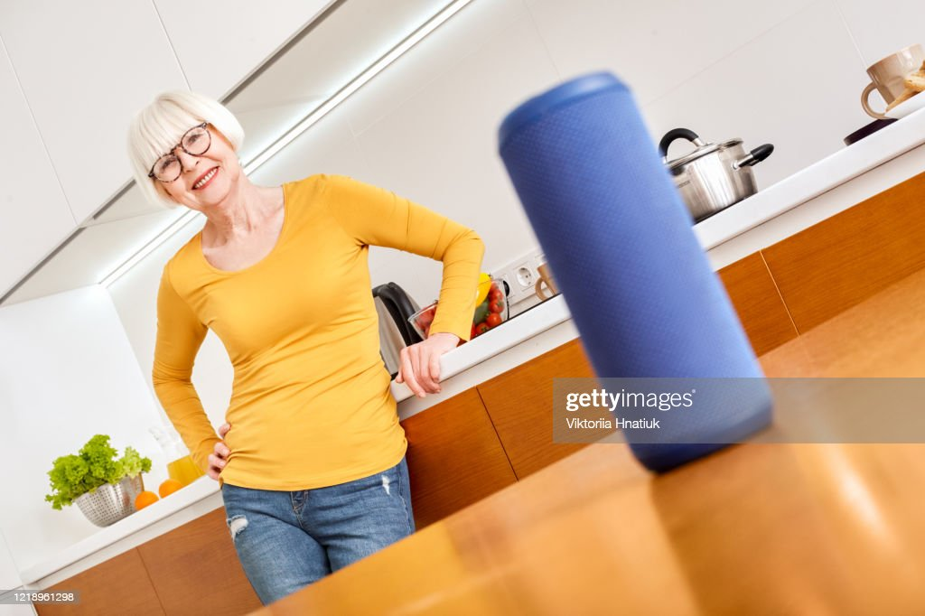 Horizontal innovation concept. Home helper indispensable detail assistant in light foreground. Elderly old woman senior style glasses controls gadget with voice listening recommendation food recipes : Stock Photo