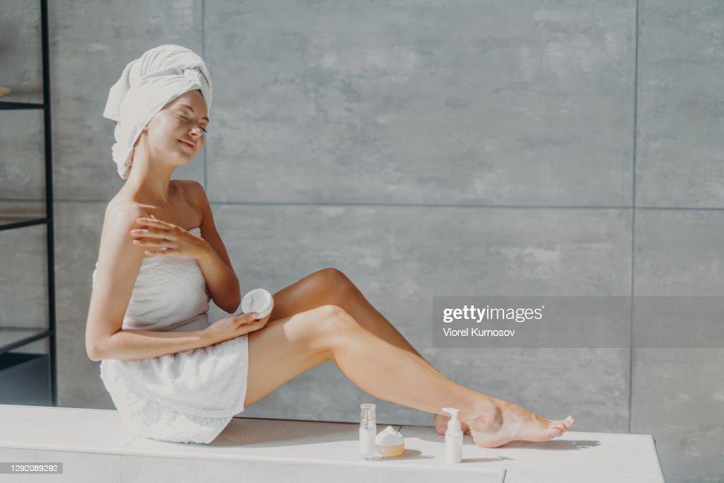 Horizontale schot van ontspannen mooie jonge vrouw verspreidt crème op de schouder, maakt gebruik van cosmetische en zorgt voor haar huid heeft slanke benen gewikkeld in badhanddoek geniet spa procedures poses met gesloten ogen : Stockfoto