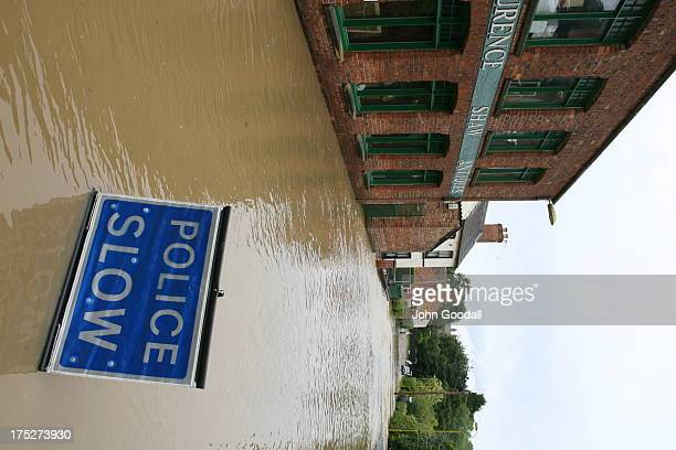CONTENT] Horncastle Lincolnshire flooded in 2007 Police slow sign blocks the road to motorists