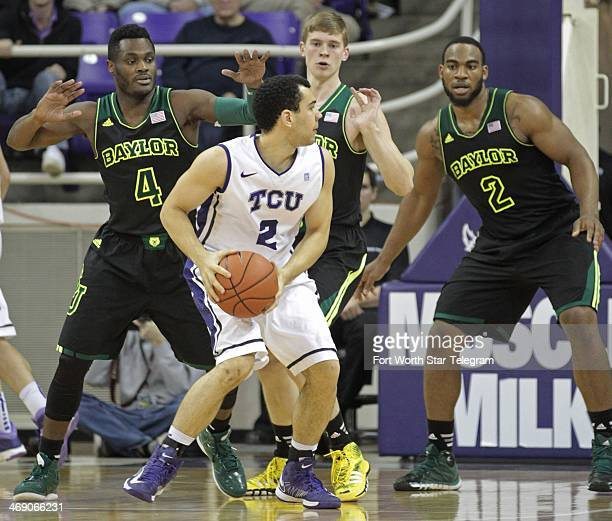 TCU Horned Frogs' Michael Williams looks to pass against Baylor Bears defenders Gary Franklin left Logan Lowery and Rico Gathers in Fort Worth Texas...