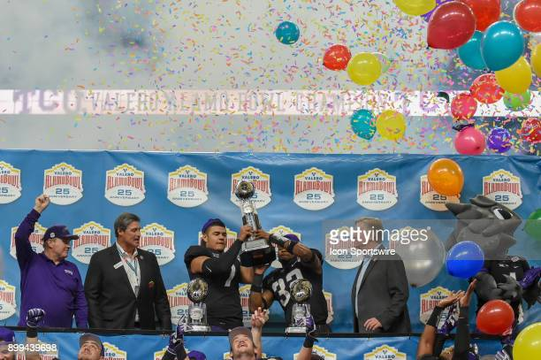 Horned Frogs quarterback Kenny Hill and TCU Horned Frogs linebacker Travin Howard hoist the championship trophy high as the balloons fall from the...