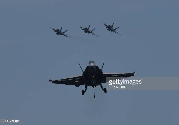 FA18 hornet fighter prepares to land while other fighter jets fly behind during a routine training aboard US aircraft carrier Theodore Roosevelt in...