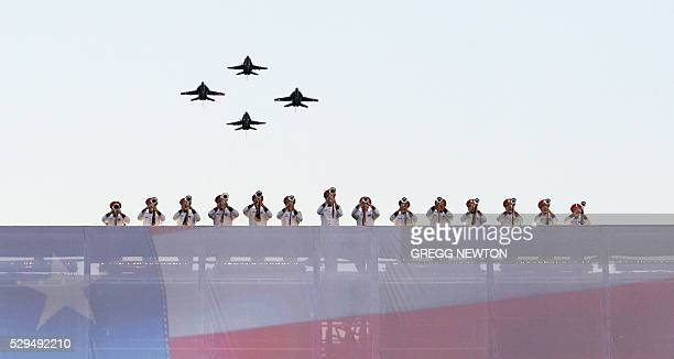 Hornets from the US Navy Strike Fighter Squadron 34 perform a flyover as trumpeters from an armed forces band perform the US national anthem during...