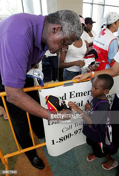 Hornets Vice President of Basketball Operations Willis Reed hands a hat to a young Hurricane Katrina evacuee housed at the Baton Rouge River center...