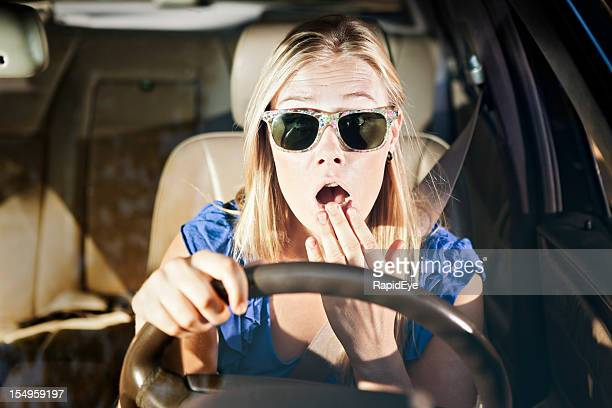 Horrified blonde driver, hand to mouth, looks through windscreen