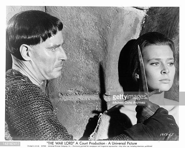 A horrified Rosemary Forsyth hears war lord Charlton Heston accept a suggestion that he have a nasty wound cauterized with a red hot dagger in a...
