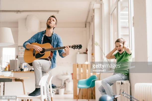 Horrified son covering his ears with father playing guitar at home