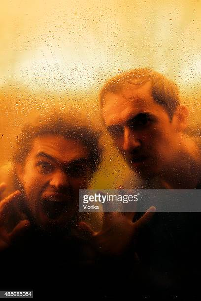 Horror concept - Screaming men looking through the rainy window