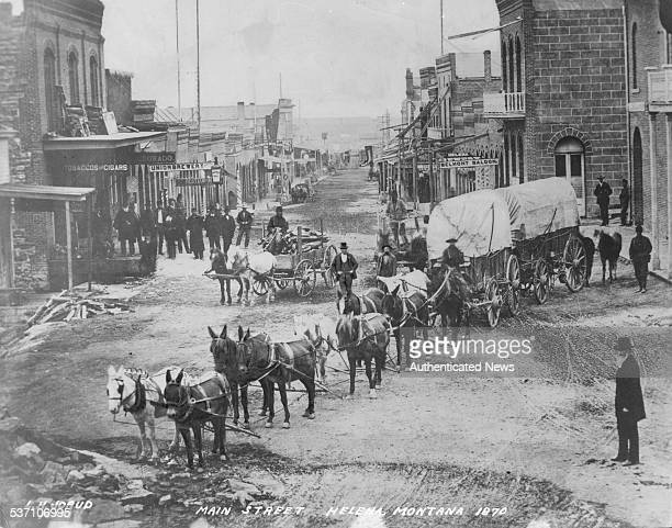 A horse and card being pulled along Main Street Helena Montana 1870