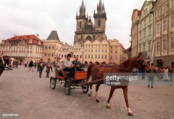 A horse and carriage rides through the Old Town Square in Prague Czechoslovakia with the Church of Our Lady before Tyn in the background