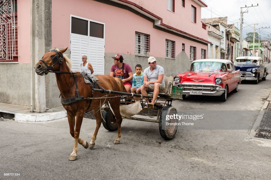 A horse and cart carry passengers in front of American muscle cars on February 2, 2017 in Matanzas, Cuba.