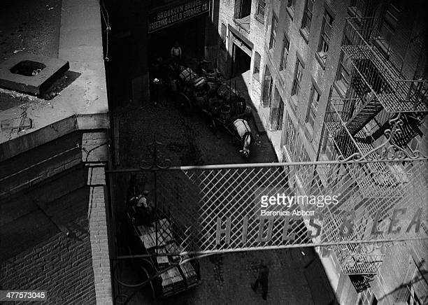 A horse and cart outside a storage company in a Lower East Side alleyway viewed from Brooklyn Bridge New York City New York circa 1930