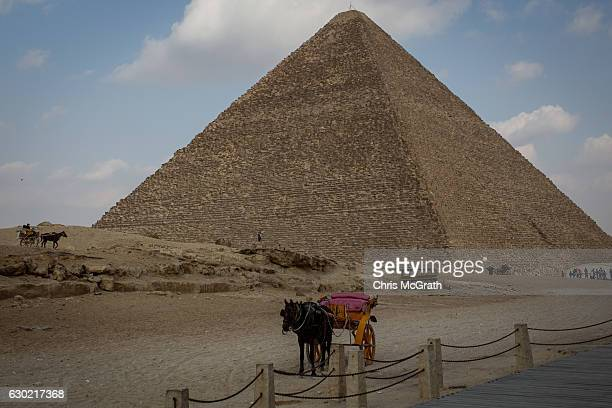 A horse and cart used for tours is seen in front of Egypt's famous Giza Pyramids on December 18 2016 in Cairo Egypt Since the 2011 Arab Spring and...