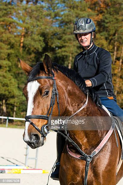 Horse and female show jumping rider on training