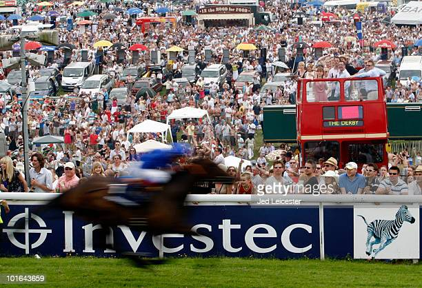A horse and jockey pass the crowds watching from the Hill infield section during the Investec Derby Festival at Epsom racecourse on June 5 2010 in...