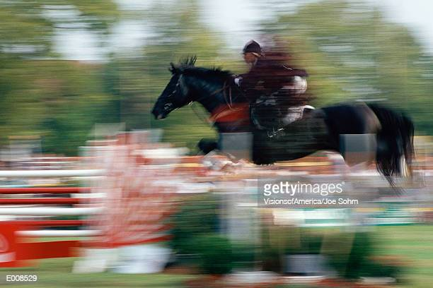 horse and rider in air jumping fence - 馬術大会 ストックフォトと画像