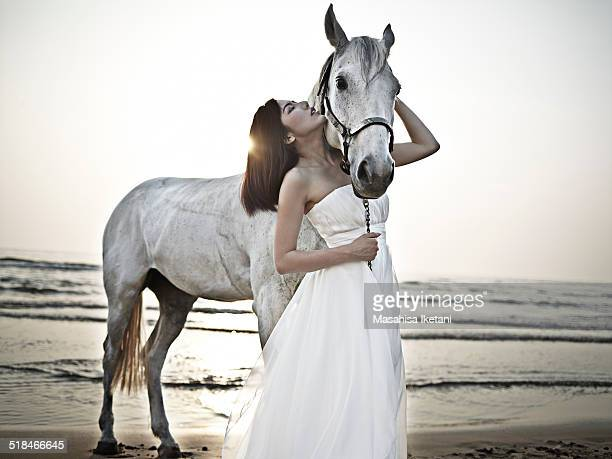 Horse and woman wearing a dress in the sea