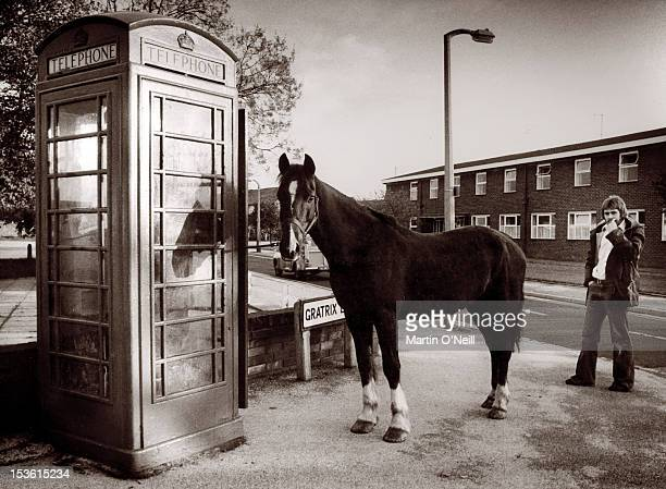 KINGDOM circa 1979 A horse appears to be waiting to use an old red phone box in Sale Greater Manchester circa 1979
