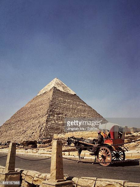 Horse Carriage At Pyramids Of Giza Against Sky