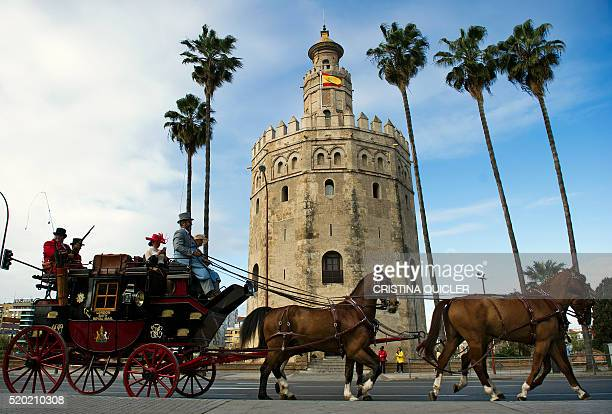 A horse carriage drives past the Giralda to participate in the XXXI Enganches exhibitiont at the Real Maestranza bullring in Sevilla on April 10 2016...