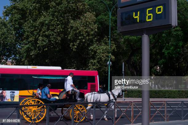 A horse carriage passes by a city digital board indicating 46 degrees Celsius in Sevilla during a heat wave on July 13 2017 / AFP PHOTO / JORGE...