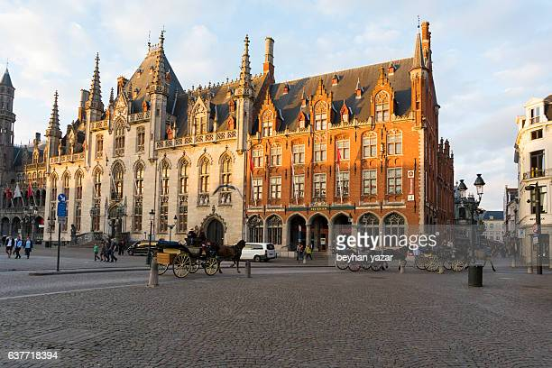 Horse carriages at downtown market plaza in brugge belgium