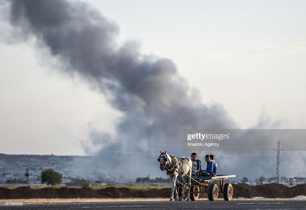 A horse cart on a road in border town Suruc of Turkey's Sanliurfa provice on October 15, 2014, as smoke rises from the Syrian border town of Kobani (Ayn al-Arab) following a US-led coalition airstrike against the Islamic State of Iraq and the Levant (ISIL).