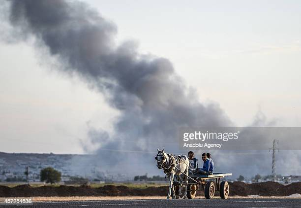 A horse cart on a road in border town Suruc of Turkey's Sanliurfa provice on October 15 as smoke rises from the Syrian border town of Kobani...