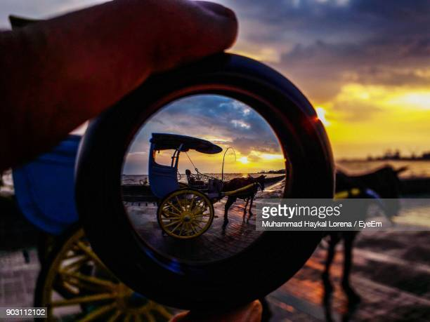 Horse Cart Seen Through Object Held By Person