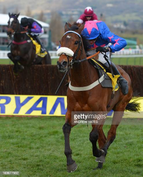 Horse 'Cue Card' ridden by Joe Tizzard jumps the last fence to win the Ryanair Steeple Chast during the third day of the Cheltenham horse racing...