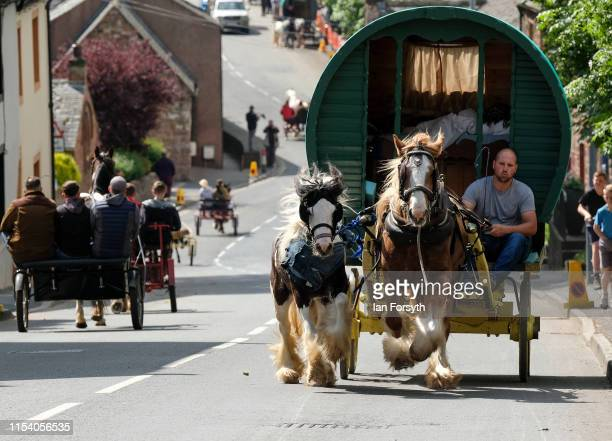 A horse drawn bow top caravan is driven through town on the first day of the Appleby Horse Fair on June 06 2019 in Appleby England The fair is an...