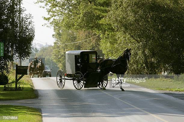 A horse drawn buggy arrives where members of the Amish community are gathering at the home of one of the girls that was killed yesterday at the one...