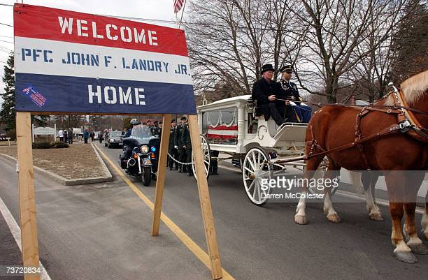 A horse drawn caisson carries the coffin of PFC John F Landry Jr through the streets of his hometown March 27 2007 in Wilmington Massachusetts Landry...