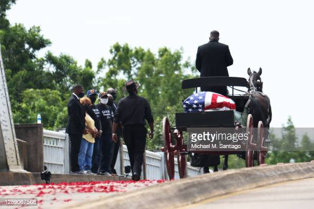 Horse drawn carriage carrying the body of civil rights icon, former US Rep. John Lewis crosses the Edmund Pettus Bridge as it prepares to pass...