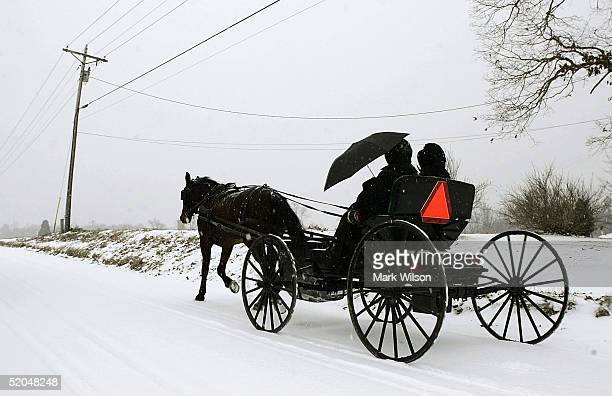 A horse drawn carriage carrying two Amish women travels down a snowy road January 22 2005 in Charlotte Hall Maryland The East Coast was hit by a...