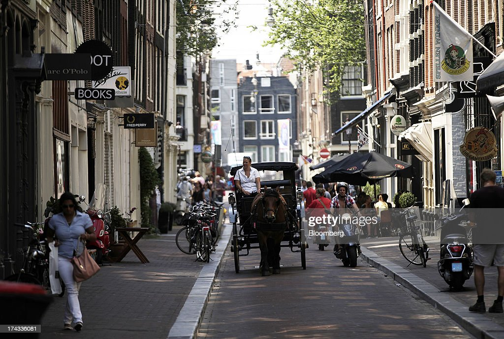 A horse drawn carriage driver looks for sightseers on a street in Amsterdam, Netherlands, on Tuesday, July 23, 2013. Dutch pension funds will be allowed to calculate liabilities on the basis of an adjusted discount rate as the government seeks to keep the retirement system viable amid low interest rates and an aging population. Photographer: Matthew Lloyd/Bloomberg via Getty Images