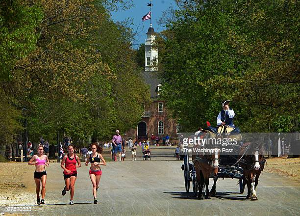 A horse drawn carriage driver tips his tricorn hat to three young women jogging past during a visit to the historic area for our travel story on...