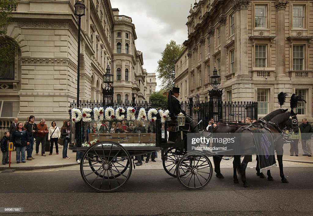 A horse drawn funeral hearse carries a floral tribute 'Democracy' in a stunt organised by a national newspaper on May 11, 2010 in London, England. British Prime Minister Gordon Brown has announced that he is to stand down as Prime Minister and Labour Party leader, adding that negotiations with the Liberal Democrats are now taking place to try and form a coalition government. Meanwhile David Cameron said that it is decision time for the Liberal Democrats to choose which party to form a Government with.