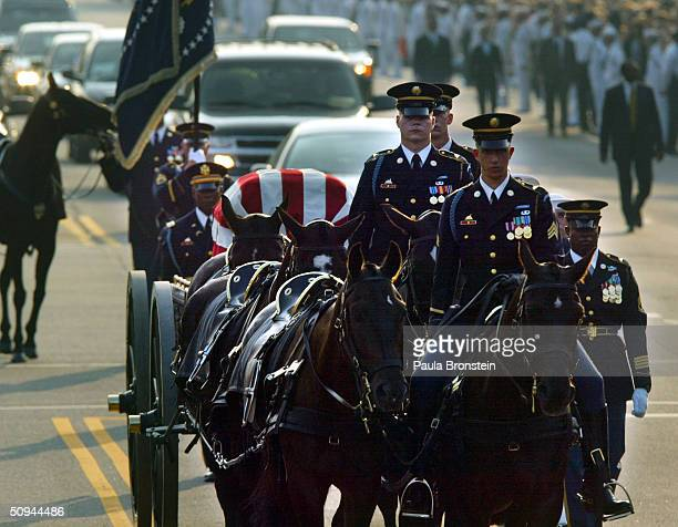 A horse drawn procession makes it way down Constitution Avenue enroute to the Capitol June 9 2004 in Washington DC carrying the body of former...