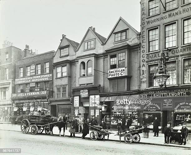 Horse drawn vehicles barrows and shop fronts 309317 Borough High Street London 1904 Men and boys wait with barrows and horsedrawn carts Behind are W...