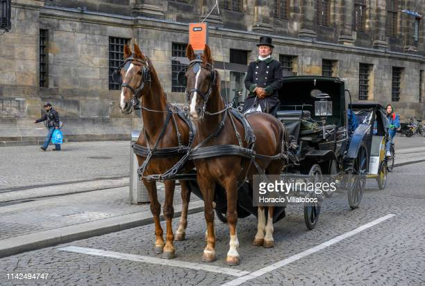 Horse driven carriage near the Royal Palace on April 13, 2019 in Amsterdam, The Netherlands. The number of visitors, some ten tourists per resident,...