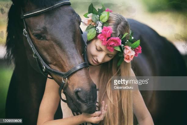 pferd umarmung lächelnde junge frau in blumenkrone - stockfoto - tierkörper stock-fotos und bilder