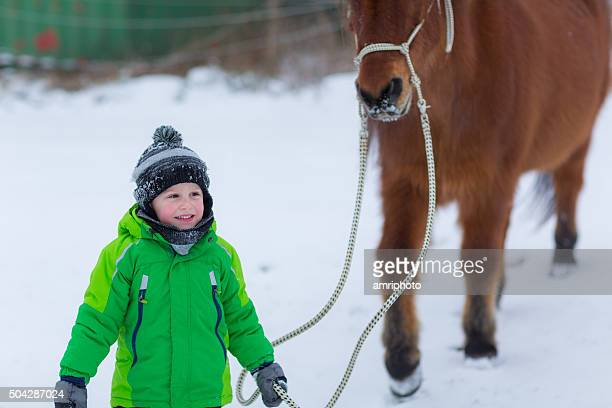 horse following young boy in winter