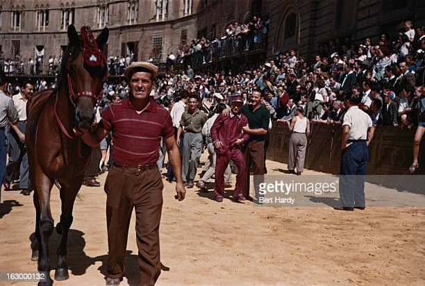 Horse is led away at the Palio di Siena, a traditional biannual horse race run in the Piazza del Campo, Siena, Italy, 1949. In the background is one...