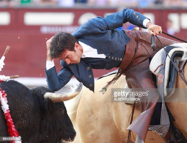 Horse mounted Spanish rejoneador Sergio Galan places his elbow on a bull's head during a bullfight in the San Isidro bullfight festival at Las Ventas...
